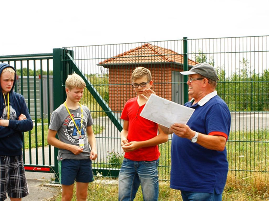 Herr Klauß Hoßfeld erläutert Jugendlichen Campusteilnehmern den Flutungsablauf und die Sicherung eines konstanten Wasserstandes im Geiseltalsee am Auslaufbauwerk bei Frankleben.