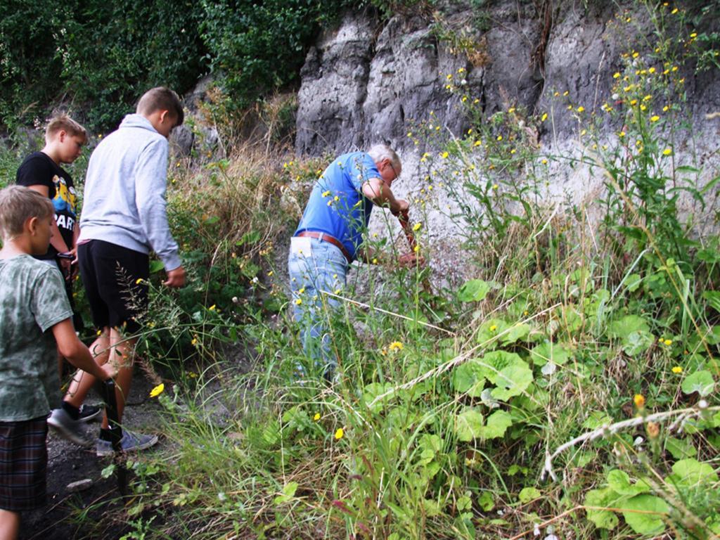 """Herr Reinhard Hirsch begleitet Jugendliche auf einer erdgeschichtlichen Entdeckungstour an den """"Geologischen Fenstern"""" in Krumpa."""
